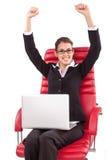 Mulher feliz com o PC nos braços vermelhos da cadeira aumentados Fotografia de Stock