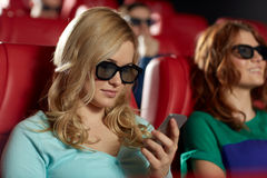 Mulher feliz com o smartphone no cinema 3d Foto de Stock Royalty Free