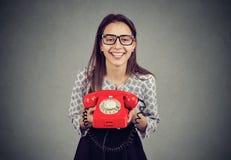 Mulher feliz com o telefone retro do vermelho do estilo imagem de stock royalty free