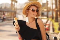 A mulher feliz com os óculos de sol vestindo do gelado e o chapéu da praia que tem o divertimento do verão durante feriados do cu imagens de stock