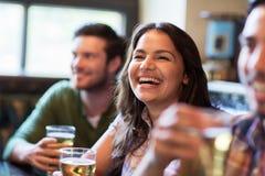 Mulher feliz com os amigos que bebem a cerveja no bar imagem de stock