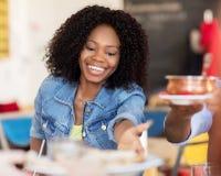 Mulher feliz com os amigos que comem no restaurante fotografia de stock