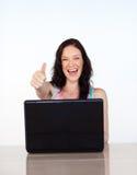 Mulher feliz com os polegares que usam acima seu portátil Fotografia de Stock