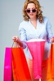 Mulher feliz com sacos de compras da cor Imagem de Stock