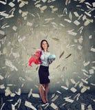 A mulher feliz com sacos de compras e o mealheiro que está sob o dinheiro chovem foto de stock
