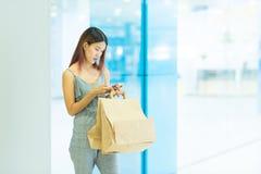 Mulher feliz com sacos de compras que aprecia na compra e que usa a manutenção programada fotos de stock
