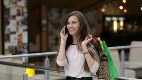 Mulher feliz com sacos de compras que fala pelo telefone video estoque