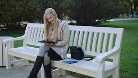 Mulher feliz com a tabuleta no parque Menina com uma tabuleta em um parque do outono em um banco vídeos de arquivo