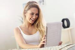 Mulher feliz com a tabuleta no sofá imagens de stock royalty free