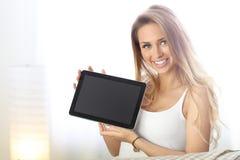 Mulher feliz com a tabuleta no sofá fotos de stock
