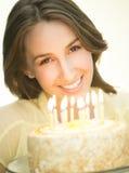 Mulher feliz com velas do Lit no bolo fotografia de stock royalty free