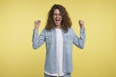 A mulher feliz comemora seu poder, abriu sua boca e gritar puxando para cima os punhos foto de stock royalty free