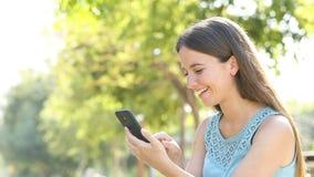 A mulher feliz consulta o índice do smartphone em um parque video estoque