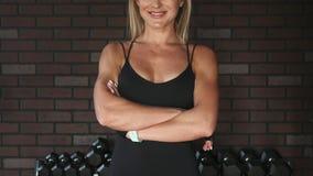A mulher feliz da aptidão cruzou seus braços no gym vídeos de arquivo
