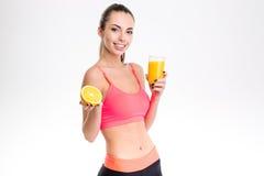 Mulher feliz da aptidão que guarda a metade da laranja e do suco Imagens de Stock Royalty Free