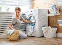 Mulher feliz da dona de casa na lavandaria com máquina de lavar imagens de stock