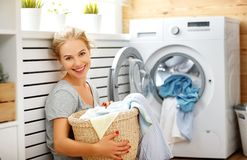 Mulher feliz da dona de casa na lavandaria com máquina de lavar fotografia de stock royalty free