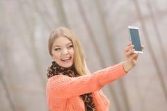 Mulher feliz da forma no parque que toma a foto do selfie Foto de Stock Royalty Free