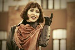 Mulher feliz da forma no revestimento de couro que anda na rua da cidade Fotos de Stock Royalty Free