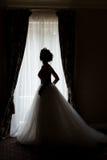 Mulher feliz da noiva 'sexy' delicada bonita com uma coroa em sua cabeça pela janela com um grande ramalhete do casamento em um b Fotografia de Stock