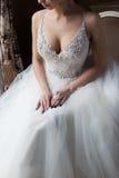 Mulher feliz da noiva 'sexy' delicada bonita com uma coroa em sua cabeça pela janela com um grande ramalhete do casamento em um b Imagem de Stock Royalty Free