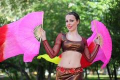 A mulher feliz dança com ventiladores do véu Fotografia de Stock Royalty Free
