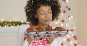 Mulher feliz de sorriso com a bandeja de queques frescos foto de stock royalty free