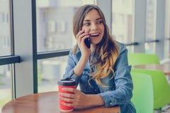 Mulher feliz de sorriso entusiástica que senta-se em um café que guarda a xícara de café, está falando no telefone com amigo, con foto de stock royalty free