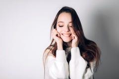 A mulher feliz de sorriso morde o bordo com um sorriso e olha para baixo no fundo branco emoções Imagem de Stock