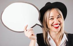 Mulher feliz de sorriso no chapéu que mantém o discurso vazio da bandeira buble para seu texto Fundo cinzento foto de stock