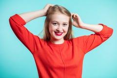 Mulher feliz de sorriso no fundo azul Menina Redheaded no vestido vermelho e nos bordos vermelhos Emoções positivas, juventude fotografia de stock