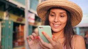 Mulher feliz despreocupada nova do moderno na menina de Straw Hat Mixed Race Tourist que usa o telefone celular em construções do filme