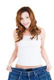 Mulher feliz do ajuste com as calças grandes, mostrando quanto peso perdeu imagens de stock royalty free