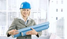 Mulher feliz do arquiteto com planta de trabalho imagens de stock royalty free