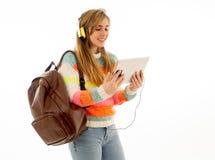 Mulher feliz do estudante nos fones de ouvido que olham a tabuleta digital que escuta a m?sica ou o curso video imagens de stock royalty free