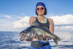 Mulher feliz do fisher com o troféu dos peixes do zander no barco fotografia de stock royalty free