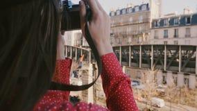 Mulher feliz do fotógrafo que toma uma foto da opinião da torre Eiffel da manhã em Paris com câmera do vintage, inclinação acima  filme
