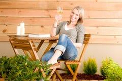 A mulher feliz do jardim aprecia o terraço de vidro do vinho Foto de Stock