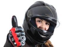 Mulher feliz do motociclista com um capacete e um polegar da estrada acima Fotos de Stock Royalty Free