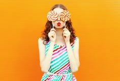 Mulher feliz do retrato que esconde seus olhos com o pirulito dois, bordos vermelhos de sopro, vestido listrado colorido vestindo fotos de stock royalty free