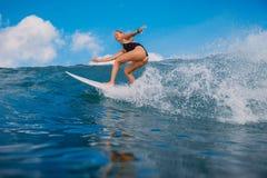 Mulher feliz do surfista na prancha na onda de oceano Surfista no oceano durante surfar imagens de stock