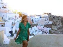 A mulher feliz do turista do curso escala as escadas em Santorini, Cycla fotografia de stock