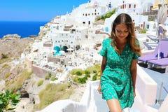A mulher feliz do turista do curso escala as escadas em Santorini, ilhas de Cyclades, Grécia, Europa Menina em férias de verão imagens de stock