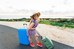 Mulher feliz do viajante com a mala de viagem na estrada e nos risos Conceito do curso, viagem, viagem Fotografia de Stock