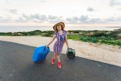 Mulher feliz do viajante com a mala de viagem na estrada e nos risos Conceito do curso, viagem, viagem Fotografia de Stock Royalty Free
