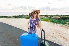 Mulher feliz do viajante com a mala de viagem na estrada e nos risos Conceito do curso, viagem, viagem Imagens de Stock