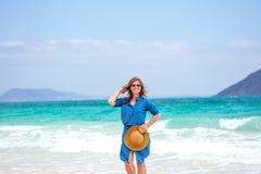 A mulher feliz do viajante no vestido azul aprecia sua praia tropical va foto de stock