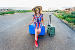 Mulher feliz do viajante que senta-se em uma mala de viagem na estrada e no sorriso Conceito do curso, viagem, viagem Imagens de Stock Royalty Free