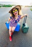 Mulher feliz do viajante que senta-se em uma mala de viagem na estrada e no sorriso Conceito do curso, viagem, viagem Foto de Stock