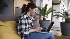 Mulher feliz durante o bate-papo video no portátil em casa A menina está sentando-se em um sofá nas calças de brim e na camisa Vi filme